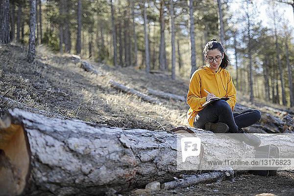 Junge Frau mit gelbem Pullover im Wald beim Schreiben