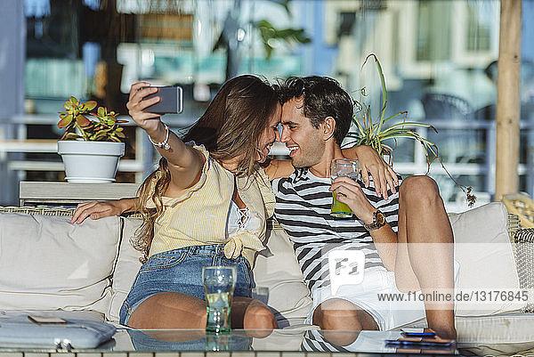 Glückliches  liebevolles junges Paar  das sich auf der Terrasse einer Bar ein Selfie gönnt