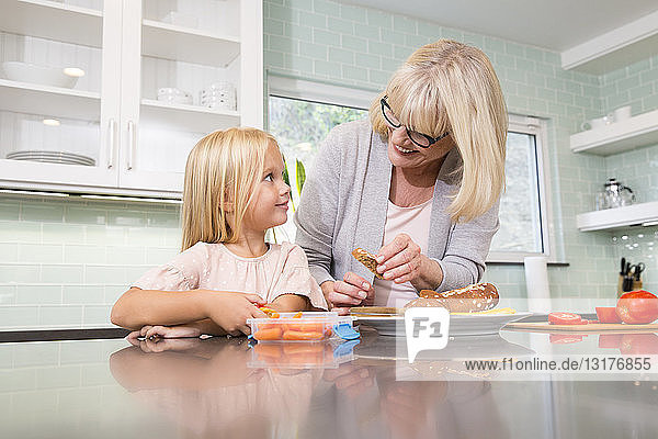 Großmutter und Enkelin bereiten gemeinsam in der Küche eine Lunchbox vor