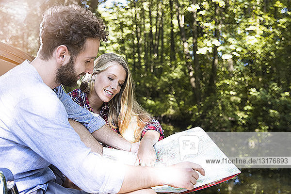 Smiling young couple reading map at a brook