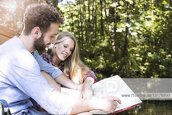Lächelndes junges Paar beim Kartenlesen an einem Bach