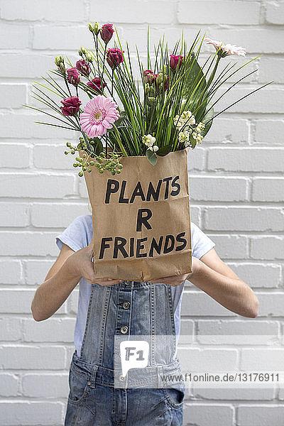 Mädchen versteckt Gesicht hinter Papiertüte mit Blumen