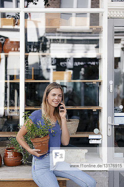 Netherlands  Maastricht  smiling young woman on cell phone in the city holding flowerpot