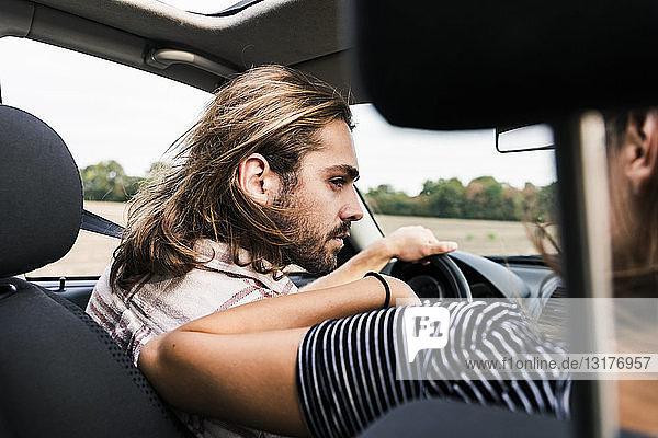 Junger Mann sieht Frau im Auto an