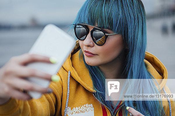 Porträt einer jungen Frau mit gefärbten blauen Haaren  die mit einem Smartphone Selbstgespräche führt