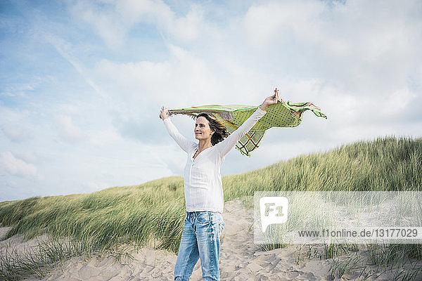 Reife Frau hält flatterndes Tuch im Wind,  Relaxiang in den Dünen