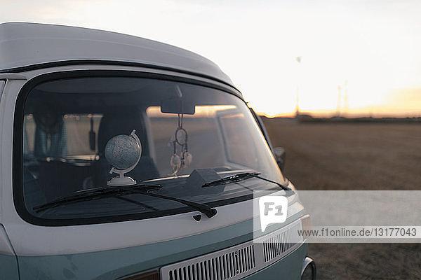 Camper van in rural landscape at sunset