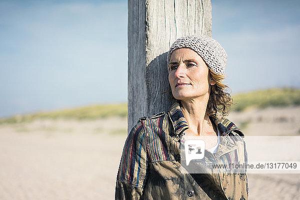 Frau mit Wollhut an Holzstange lehnend