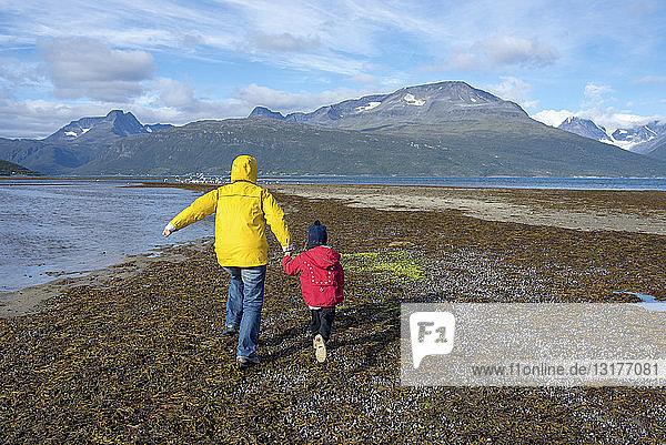 Norwegen  Mutter und Tochter laufen am Strand  Lyngenfjord