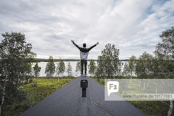 Finland  Lapland  man standing on roof of a house at a lake with raised arms
