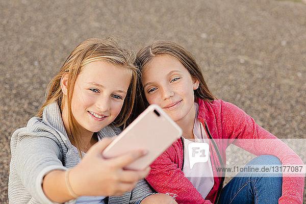 Porträt von zwei lächelnden Mädchen  die sich mit einem Smartphone selbstständig machen