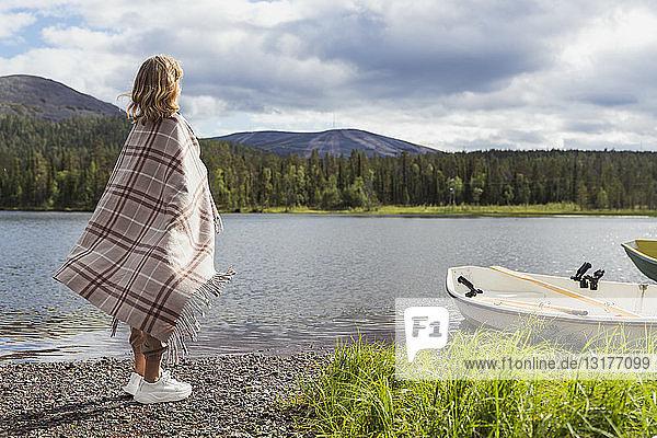 Finnland  Lappland  Frau in eine Decke gewickelt am Seeufer stehend