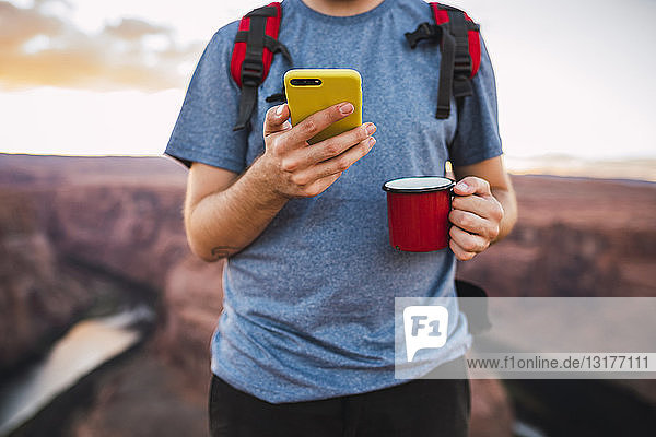 Young man holding red cup and using smartphone