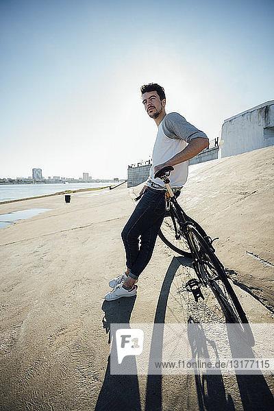 Junger Mann mit Pendler-Fixie-Fahrrad macht Pause an Betonmauer