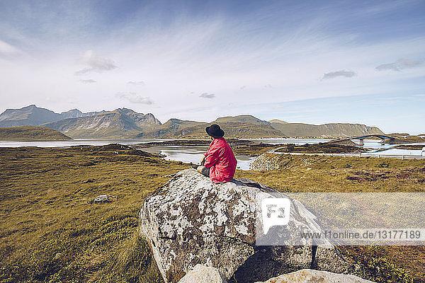 Norway  Lofoten  man wearing red rainjacket sitting on a rock looking at view