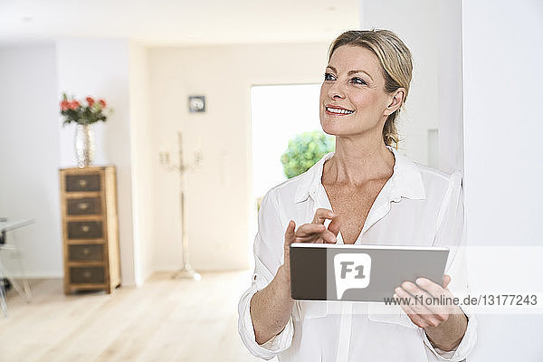 Smiling woman using tablet at home