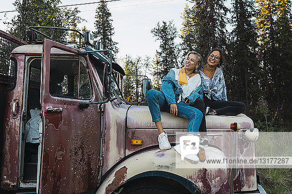 Two friends sitting on a broken truck