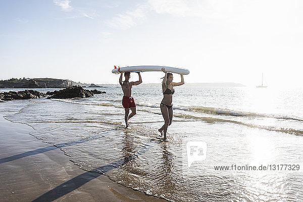 Frankreich  Bretagne  junges Paar mit einem SUP-Board gemeinsam auf See
