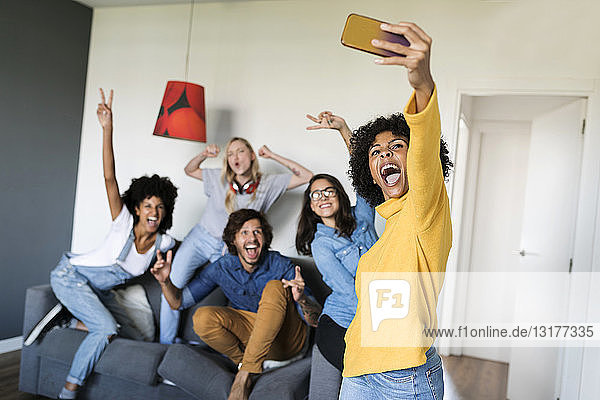 Cheerful friends taking a selfie at home