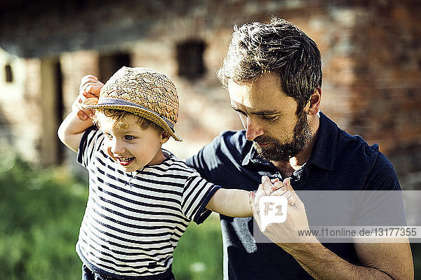 Father assisting his little son in balancing on a fence