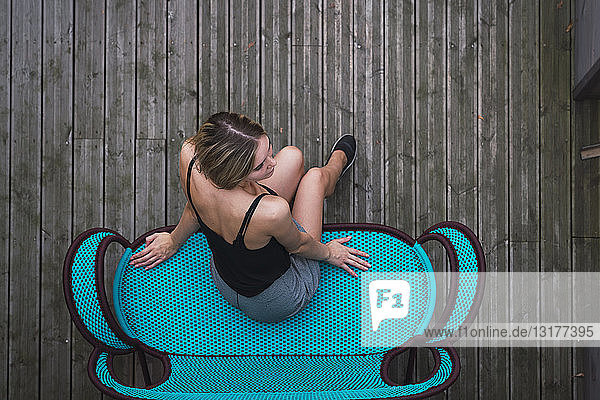 Young woman sitting on turquoise couch on terrace  top view