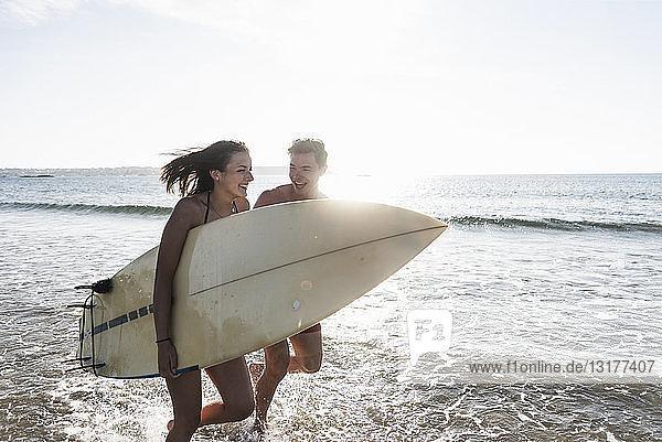 Frankreich,  Bretagne,  glückliches junges Paar mit im Meer laufendem Surfbrett