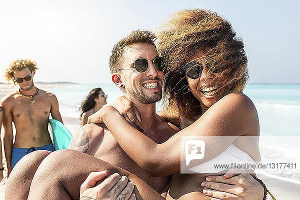 Freunde gehen am Strand spazieren  ein Mann trägt seine Freundin