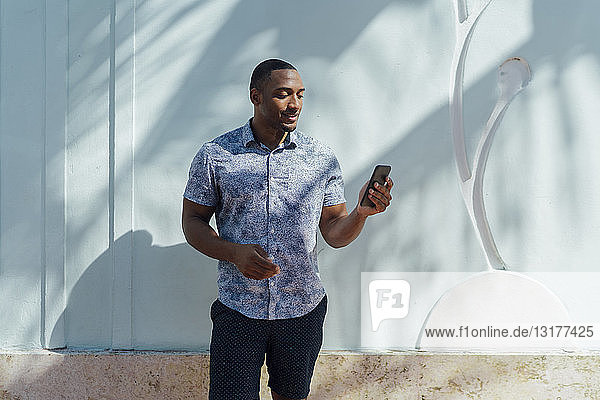 Smiling young man wearing shirt looking at cell phone at a wall