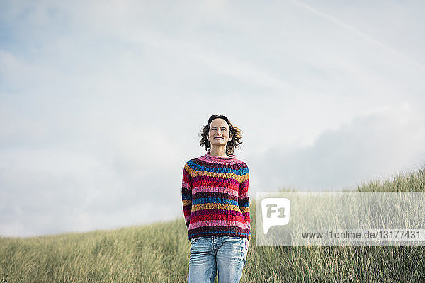 Zufriedene Frau steht in den Dünen und lächelt