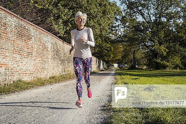 Ältere Frau läuft in einem Park an einer Ziegelmauer entlang