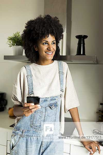 Smiling woman holding cell phone in kitchen at home