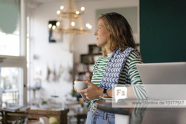 Junge Frau mit Tasse Kaffee und Laptop in einem Cafe