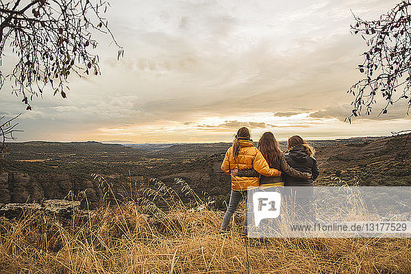Spain  Alquezar  three friends embracing on a hill overlooking the scenery