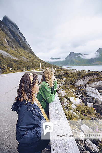 Norway  Senja  two young woman standing at the roadside looking at view