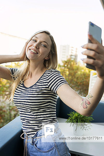 Smiling young woman taking a selfie on balcony