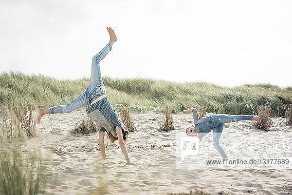 Mutter und Tochter amüsieren sich am Strand beim Radschlagen