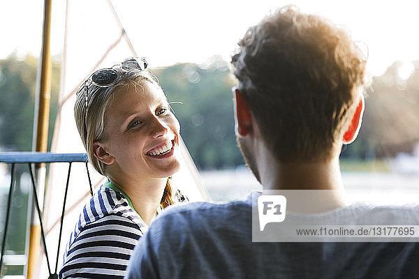 Young woman laughing at man at a lake next to sailing boat