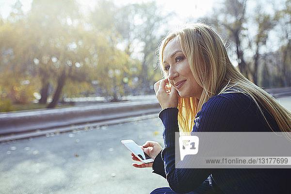 Porträt einer zufriedenen blonden Frau mit Smartphone im herbstlichen Stadtpark