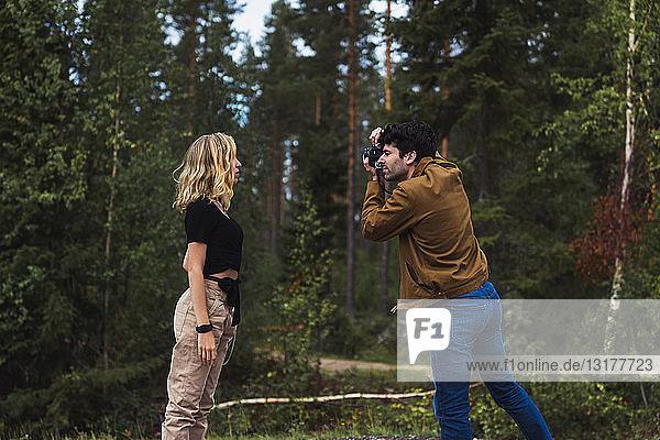 Finnland  Lappland  Mann fotografiert Frau in ländlicher Landschaft