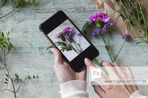 Frauenhände beim Fotografieren von Blumen mit dem Smartphone