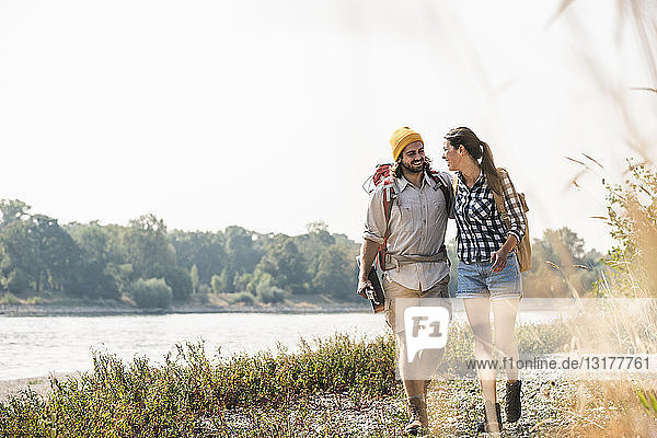 Glückliches junges Paar mit Rucksäcken und Gitarre beim Spaziergang am Flussufer