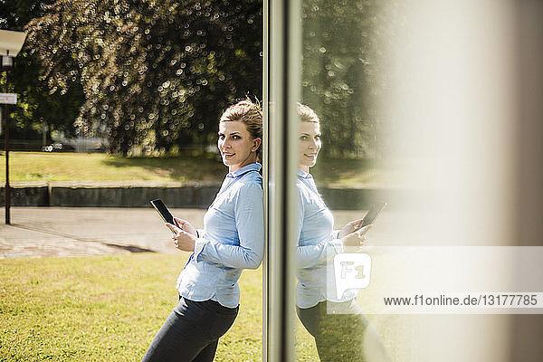 Lächelnde Frau lehnt an Glasfront und hält Tablett