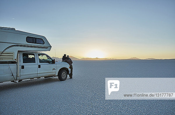 Bolivien  Salar de Uyuni  Mutter und Sohn im Wohnmobil am Salzsee bei Sonnenuntergang