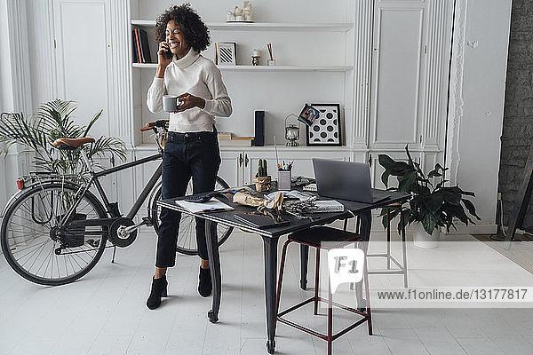 Mittlere erwachsene Freiberuflerin  die in ihrem Heimbüro steht  Kaffee trinkt und telefoniert