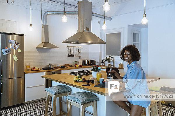 Woman having breakfast in her kitchen  eating fruit
