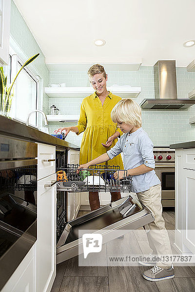 Junge hilft Mutter beim Abräumen des Geschirrspülers in der Küche
