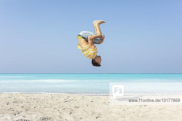 Junger Mann macht einen Salto am Strand