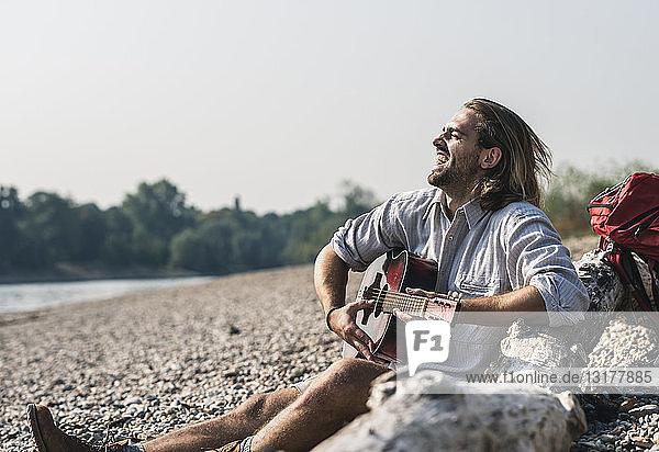 Überschwänglicher junger Mann sitzt am Flussufer und spielt Gitarre