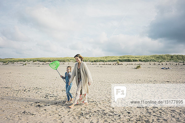 Mutter und Tochter gehen mit einem Sprungtuch zum Meer