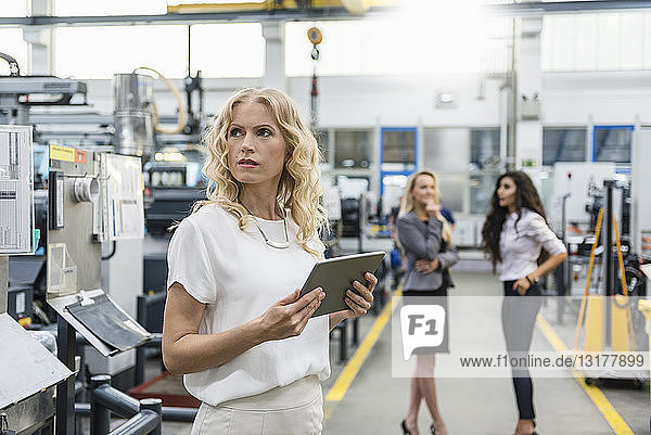 Woman holding tablet in factory shop floor with two women in background